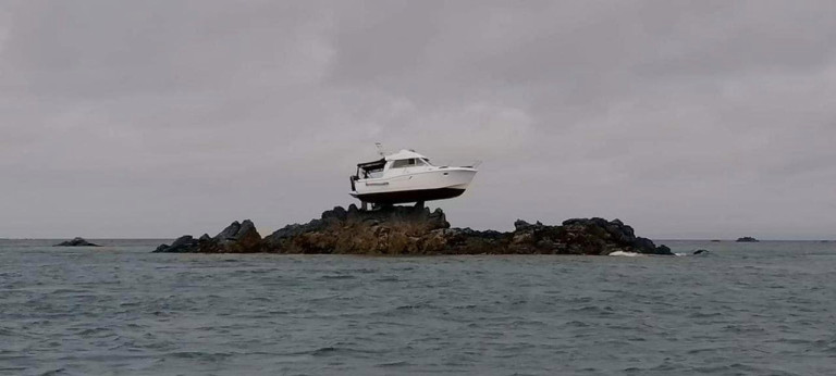 Picture of a boat that got marooned on top of rocks on Ecrehous mini islands, off the coast of Jersey, Channel Islands.