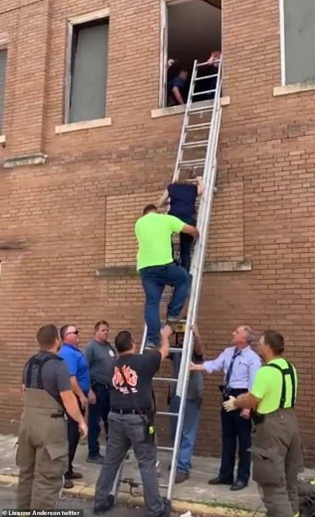 Easy does it: With assistance from the team below, McEntire climbed down the ladder and appeared to be in good spirits despite the traumatic event