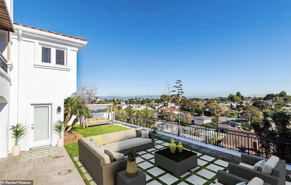 The home also includes an outdoor terrace with grassy area and tiled deck