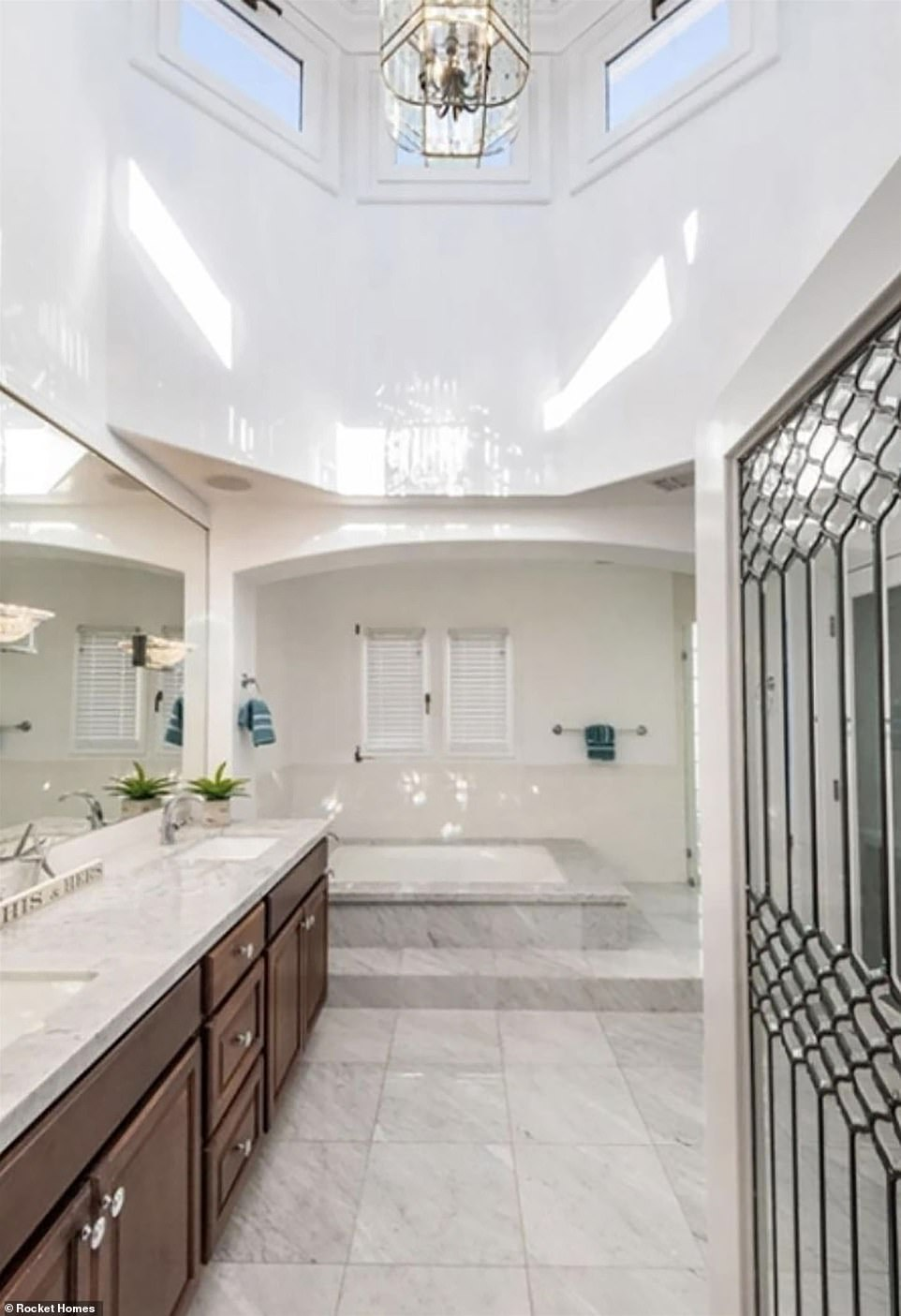 The bathroom in the master bedroom includes a marble floor with tub and clerestory windows allowing for natural light