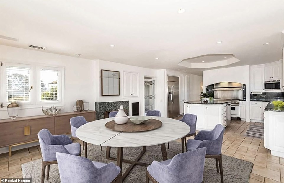 The second level has wooden floors and a kitchen with an island and adjacent dining area