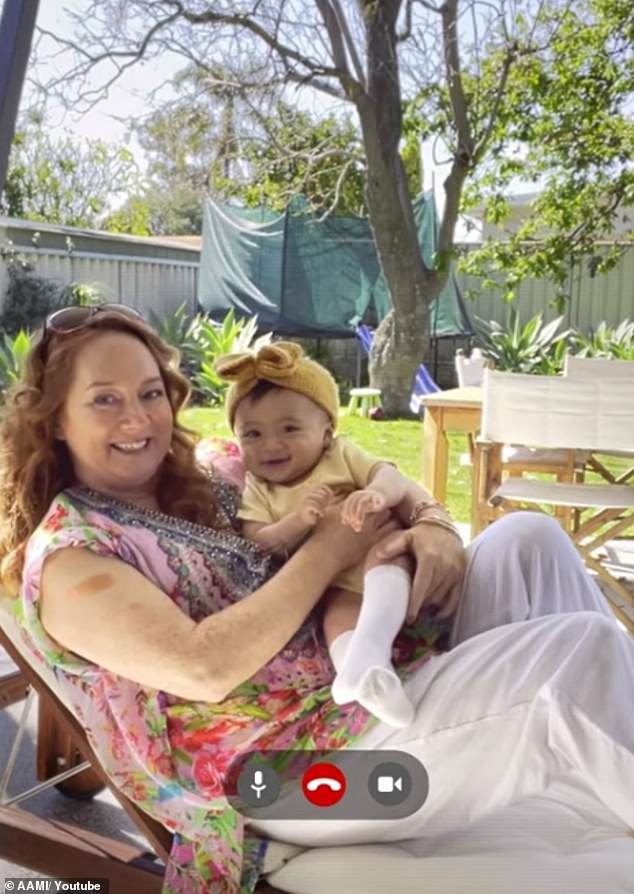 Adorable new addition to the family: He then turns the camera to show Rhonda reclined on a sun lounge dressed in an intricate kaftan as she cradled their child.'What daddy said huh,' she says to their little one, adding: 'Vax up Australia, like a sunrise'