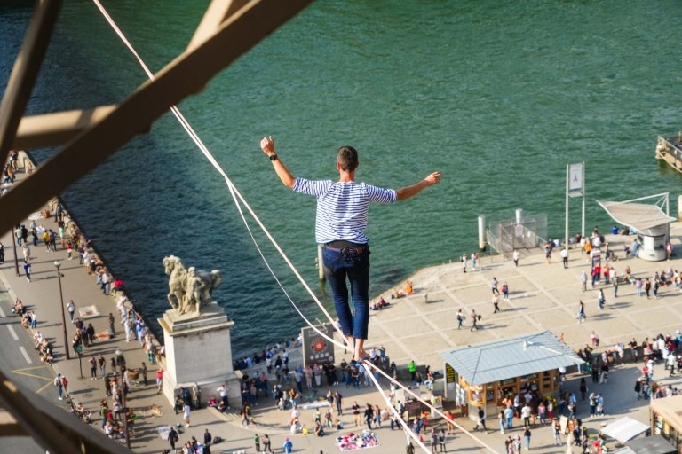 Tightrope walker Nathan Paulin traverses a slackline between the Eiffel Tower and the Trocadero Square, on September 18, 2021 in Paris, France.