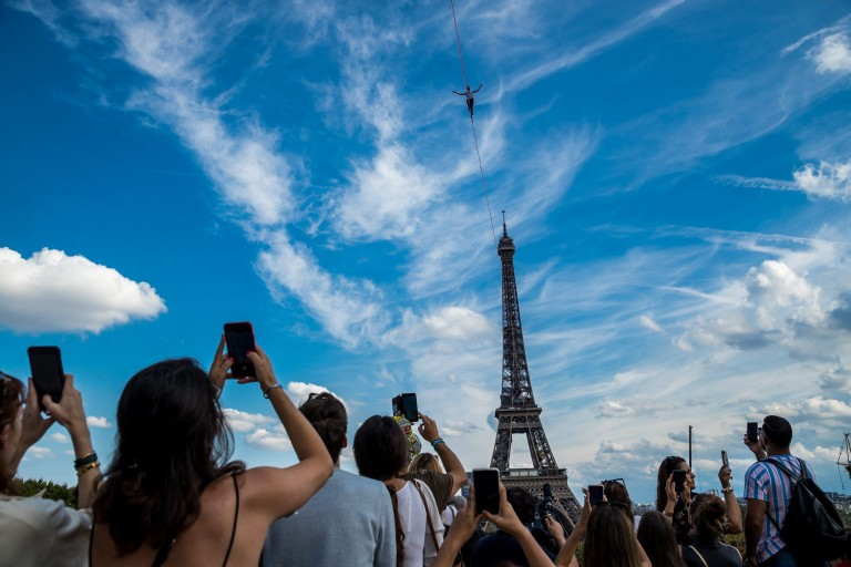 Crowds watch tightrope walker Nathan Paulin traverses a slackLine between the Eiffel tower and the Chaillot Theater.