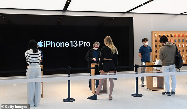 Customers wait for their new iPhone while complying with social distancing inside the Apple Store on George Street on September 24, 2021 in Sydney