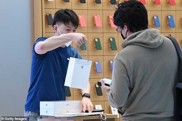 Jun Matsuda receiving his new Apple products from an Apple staff member inside the Apple Store on George Street on September 24, 2021 in Sydney, Australia