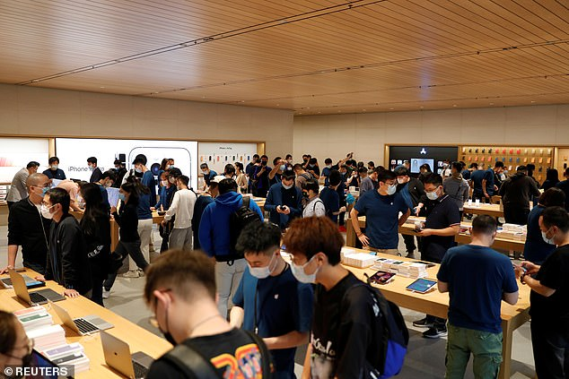 People wear face masks at an Apple Store on the day the new Apple iPhone 13 series goes on sale, in Beijing, China