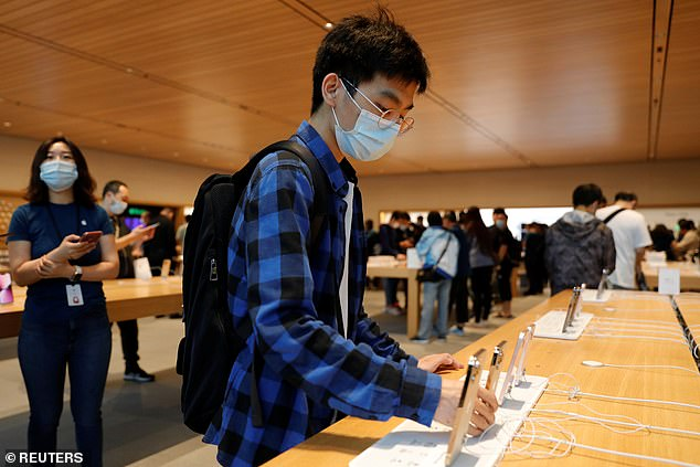 A customer wearing a face mask looks at an iPhone 13 at an Apple Store on the day the new Apple iPhone 13 series goes on sale, in Beijing, China