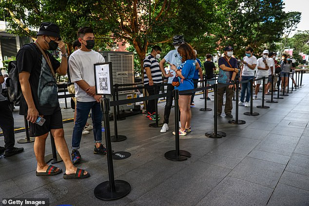 People wait in line to purchase newly released products at the Apple Store in Orchard Road on September 24, 2021 in Singapore