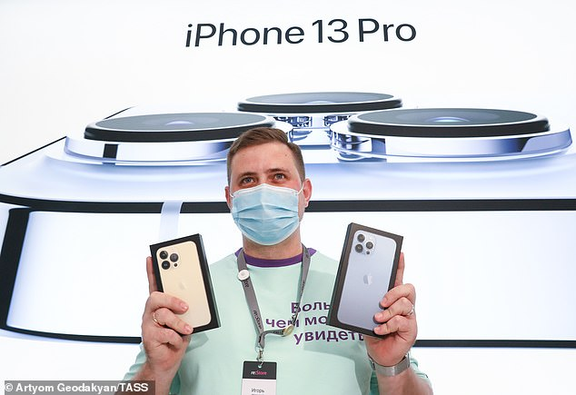 The iPhone 13 has six cores and a specialized portion for running artificial intelligence algorithms. And the iPhone 13 and iPhone 13 mini both have larger batteries to give them more power than their predecessors. Pictured, a shop assistant in Russia