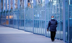 A woman wearing a protective face mask walks along a deserted city bridge during morning commute hours on the first day of a lockdown as the state of Victoria looks to curb the spread of coronavirus.
