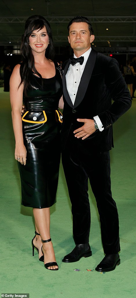 Engaged: Katy cozied up to her fiance Orlando Bloom, who looked dapper in a velvet tuxedo