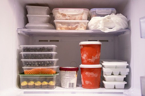A freezer shelf with containers of food