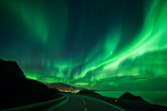 intense northern lights over an empty street, which stretches out far to sea