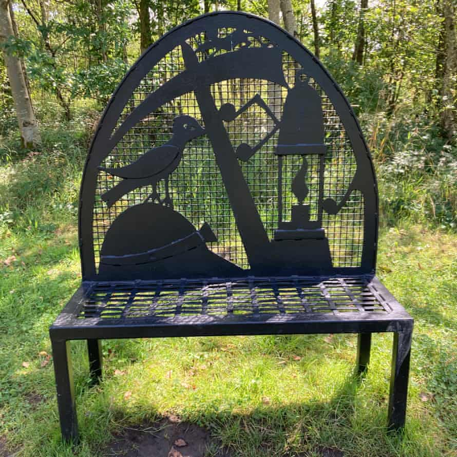 A bench along the path featuring symbols of the area's mining history, Merseyside, UK
