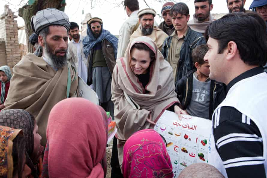 UNHCR Goodwill Ambassador Angelina Jolie presents education materials to local Headteacher, Gul Rahman, and young schoolgirls in the village of Qala Gudar, Qarabagh District February 2011 some 28km outside Kabul, Afghanistan.