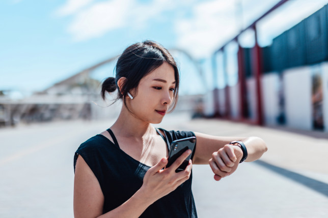 Young woman using smartwatch and doing outdoor workout in the city
