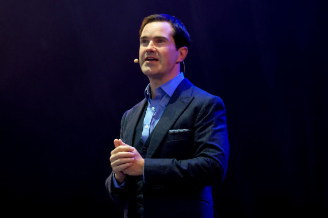 Jimmy Carr on stage face away from the camera in a suit