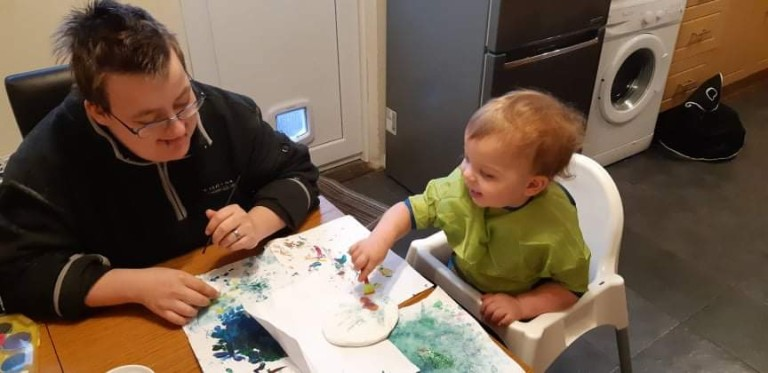Jacob Bouyer is sat at a table while their child is pictured in a high chair beside him playing with paint