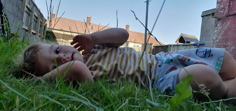 Jacob Bouyer's child is pictured lying in some grass on a sunny day, he is looking at the camera
