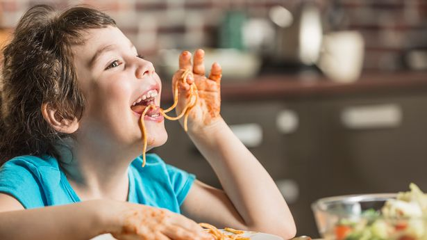Cheerful little girl eating spaghetti with hands at home