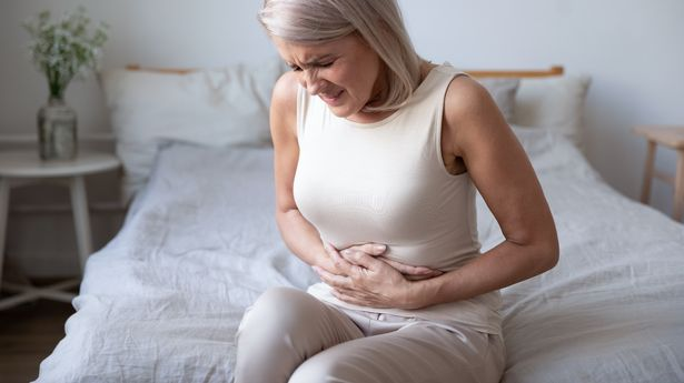 A woman in pain holding her stomach