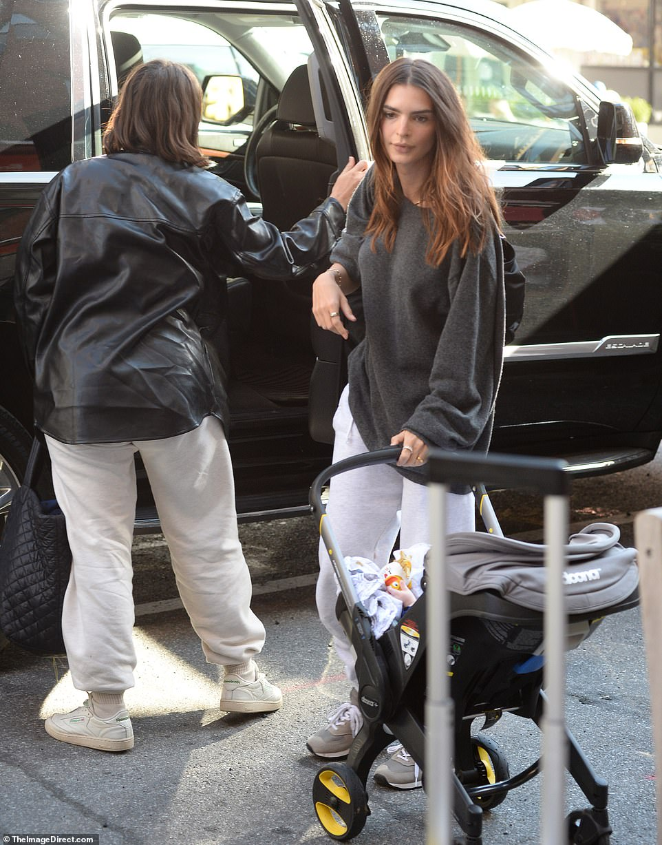 Emily Ratajkowski is pictured in New York City Saturday with her seven-month-old son in a stroller and a companion