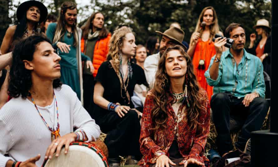 Guests at the Medicine festival near Berkshire, UK, take part in a storytelling and song session around a fire circle, during the daytime.