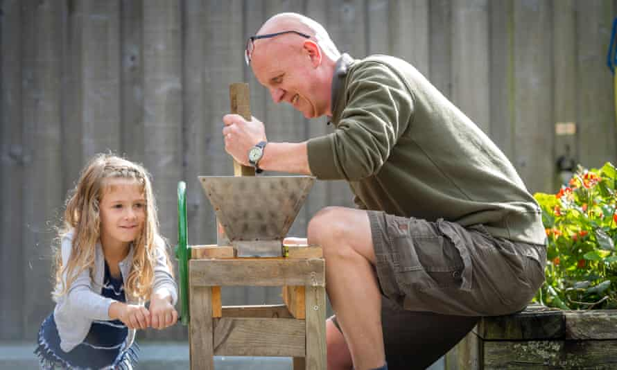 A man and young girl operating an apple press