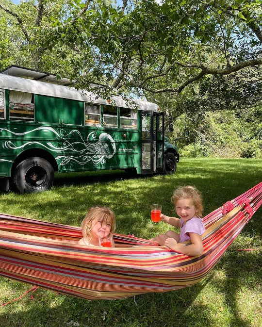 Pepper and Violet outside the school bus sitting in a hammock