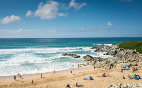 Colour image of families enjoying their holiday on Fistral beach, Cornwall, England.