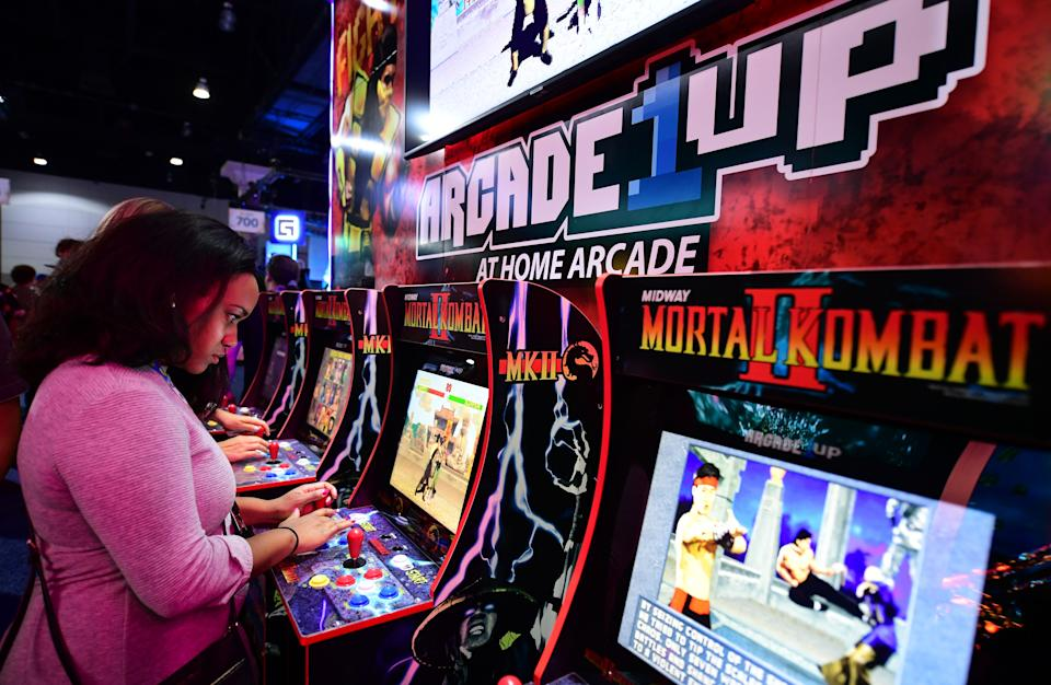 Woman plays video gabe Mortal Kombat II in an arcade
