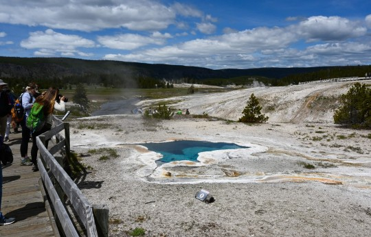 Tourists take pictures of the Blue Star spring near Old Faithful Upper Geyser Basin in Yellowstone National Park in Wyoming on June 11, 2019. - Old Faithful has erupted every 44 to 125 minutes since 2000. (Photo by Daniel SLIM / AFP) (Photo credit should read DANIEL SLIM/AFP/Getty Images)