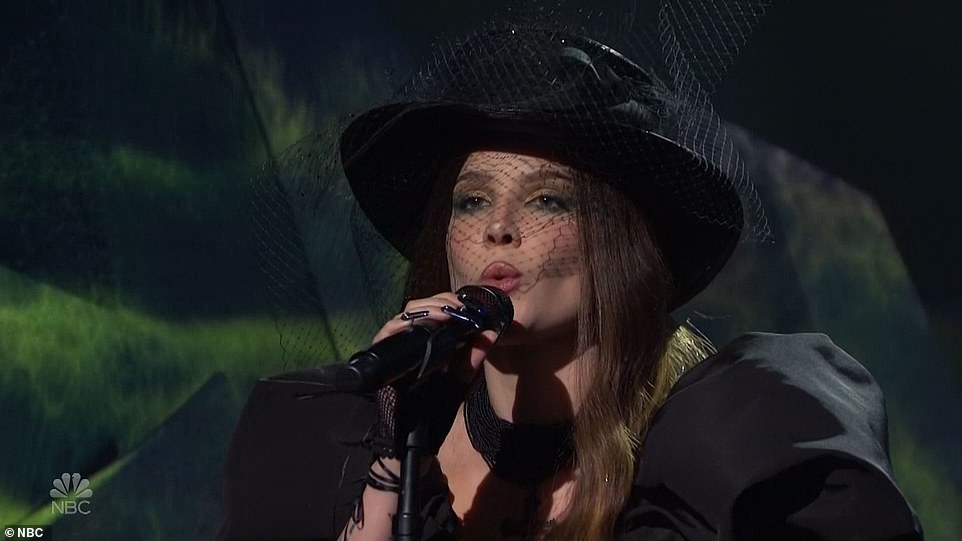 Back in black:She was dressed in a voluminous black dress and a wide-brimmed hat with a veil while singing her ballad Darling