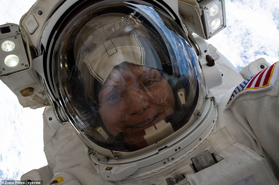 NASA's Anne McClain, grinning broadly with her visor up, floats 260 miles above the surface of the Earth during an excursion to upgrade the power storage capacity of the ISS on March 22, 2019. This was McClain's first spacewalk.