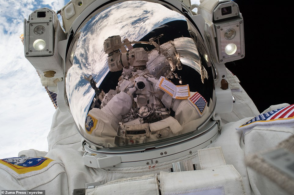 Mark Vande Hei, pictured here with his visor down, captures the Earth and the ISS in another selfie taken on January 23, 2018.
