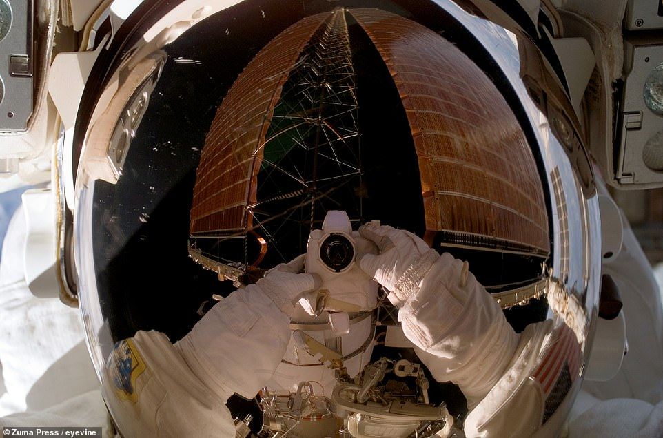 NASA's Sunita Williams captures one of the ISS's 122-foot (37-meter) -long solar power arrays in her reflective helmet visor.