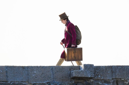 BNPS.co.uk (01202 558833) Pic: Graham Hunt/BNPS Date: 11th October 2021. Pictured: Timoth??e Charlamet who is playing the young Willy Wonka is seen walking along the top of the Cobb harbour wall with a suitcase. Hollywood heartthrob Timothee Chalamet is seen stepping out into his latest role of playing Willy Wonka. The Oscar-nominated actor was captured wearing the distinctive purple velvet overcoat and top hat favoured by Roald Dahl's chocolate-making character. The 25-year-old is playing a younger version of Willy Wonka before the chocolate factory was created. The first day of filming took place today in Lyme Regis, Dorset, which has already been covered in fake snow for the event.