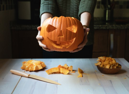 Carved pumpkin for Halloween, with leftover pumpkin flesh on a table