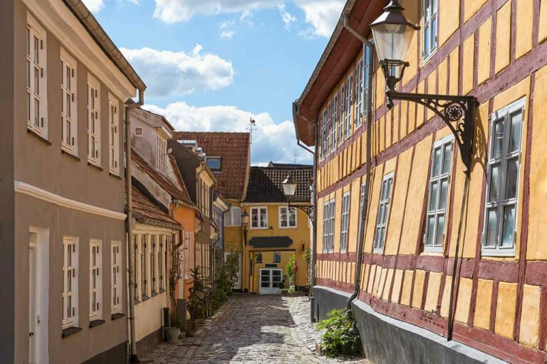 Cobblestone street with slanted houses at the old town of Aalborg, Denmark