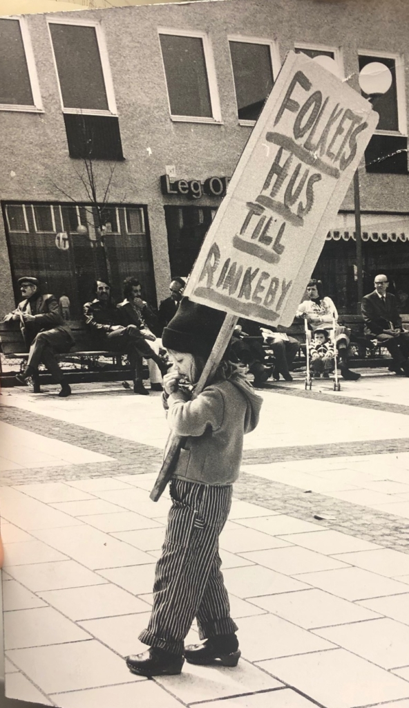Litet barn bär på ett plakat med texten Folkets Hus till Rinkeby.