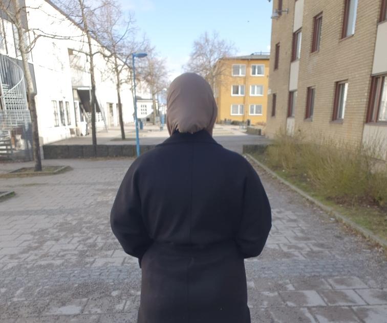 Kvinna i hijab fotograferad bakifrån.