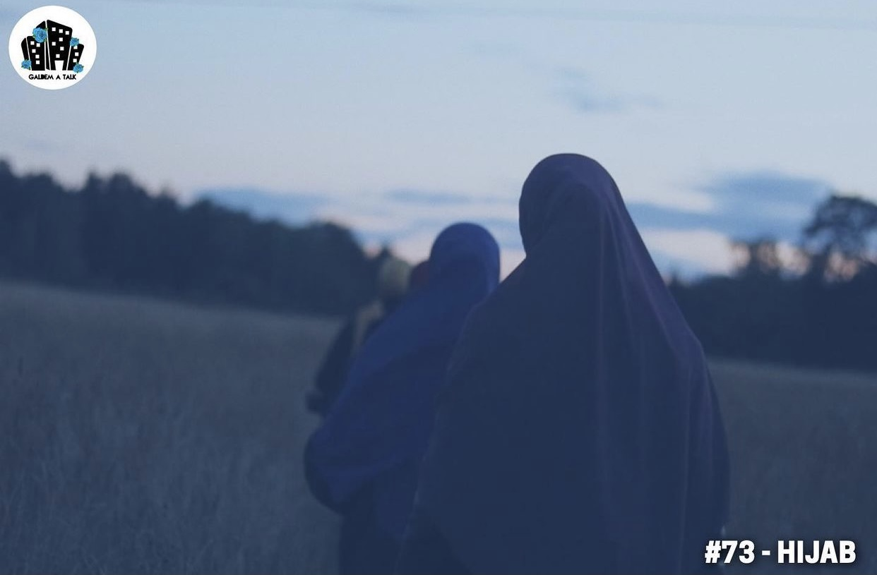 Kvinnor bakifrån i hijab på ett fält