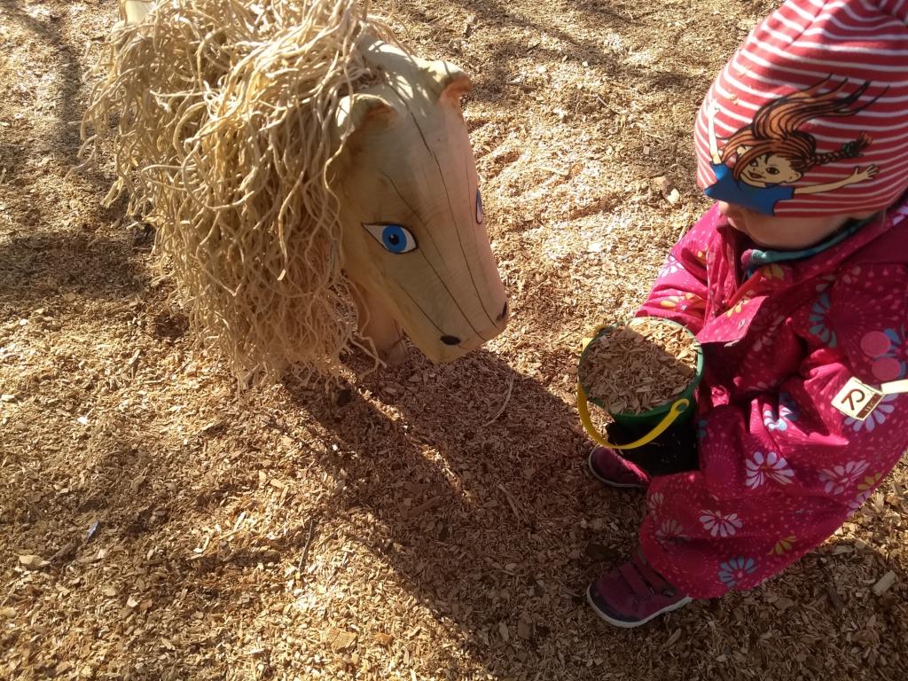 Ett barn leker med en häst av trä i parkleken RInken