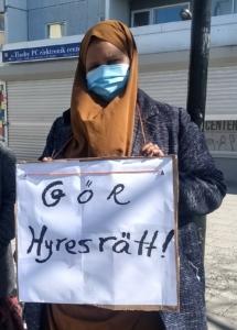 En kvinna med munskydd håller en skylt med texten Gör hyresrätt