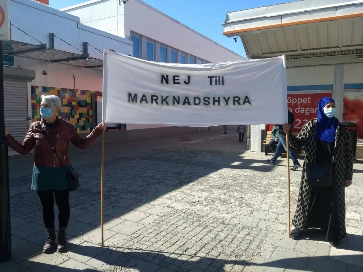 Två kvinnor med munskydd håller en banderoll med texten Nej till marknadshyra