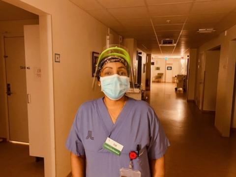 Undersköterska i munskydd och visir.