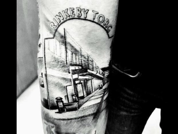 Stor tatuering på en arm av Rinkeby centrum