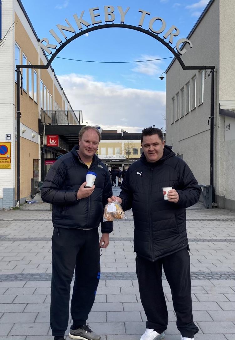 Två män med kaffemuggar i händerna på Rinkeby torg.