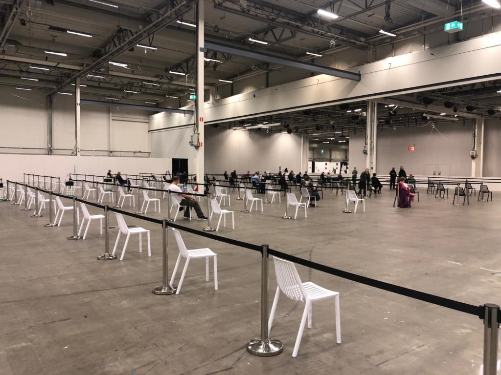 stor hall med massor med stolar, på några sitter folk.
